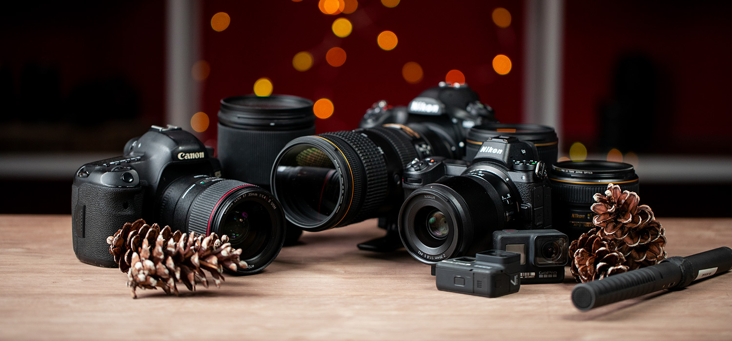 Canon and Nikon Gear on Table with Pine Cones